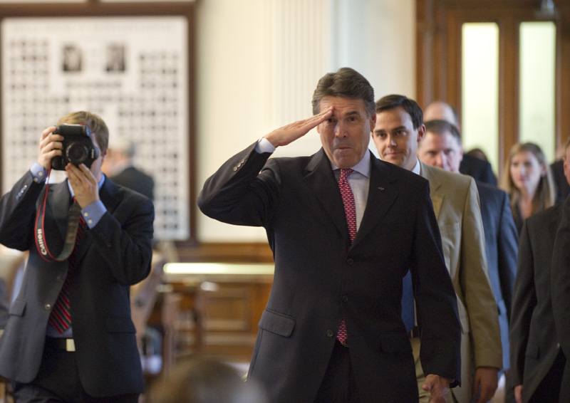 Gov. Rick Perry makes a playful salute to the son of State Rep. Craig Eiland, D-Galveston, as he walked through the House chamber on his way to a meeting with House Speaker Joe Straus at noon on May 19, 2011.