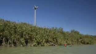Security camera towers loom over the Rio Grande River.