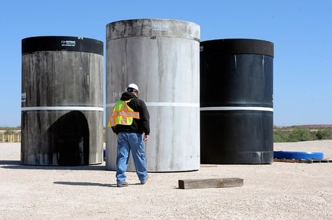 John Ward, operations project task manager at Waste Control Specialists' facility near Andrews, Texas, walks over to inspect concrete canisters that will house drums of nuclear waste.
