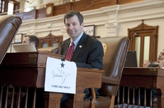 "State Rep. David Simpson, R-Longview, sits at his desk on the House floor with an airplane drawing and the ""Come and Take It"" slogan visible on May 27, 2011."
