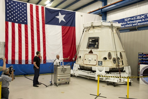 NASA administrator Charles Bolden, right, shows off the Dragon spacecraft as SpaceX CEO Elon Musk, left, listens in McGregor, TX on June 13, 2012.