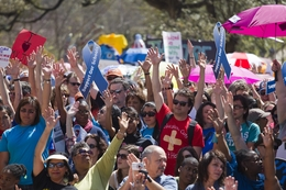 Texas teachers raise their hands during the Save Our Schools rally at the Texas Capitol on March 12, 2011