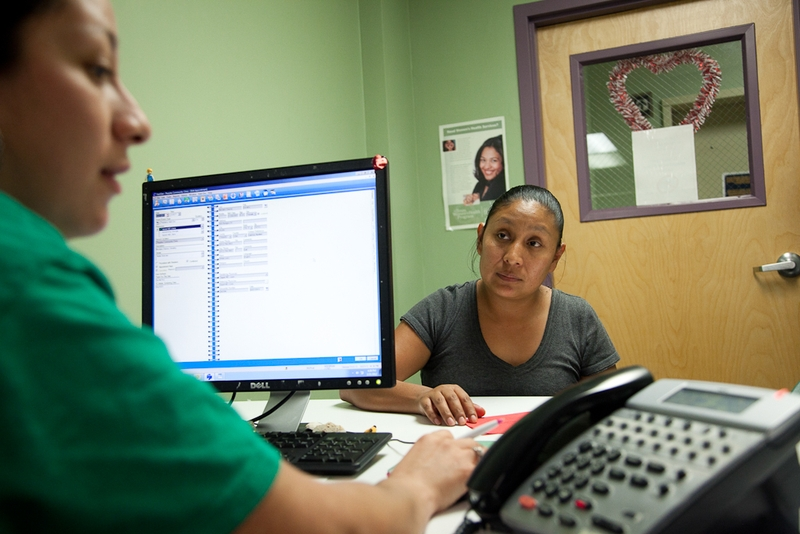 Nancy Sebrian, a patient service representative at The People's Community Clinic helps Angelina Chavez fill out paperwork. The Community Health Assistance Program, a program that helps Texans get access to insurance, will run out of federal grant money in a few weeks.