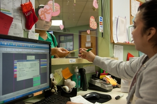 A patient at The People's Community Clinic pays her bill as the cashier's desk.  The Community Health Assistance Program, a program that helps Texans get access to insurance, will run out of federal grant money in a few weeks.