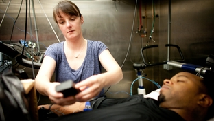 Becky Lucas, post doctoral fellow, assists in the set up of the environmental chamber, Antionne Williams, 31, volunteer research subject,  lies in for heat exposure as part of  research at the Institute for Exercise and Environmental Medicine at Presbyterian Hospital in Dallas, Friday September 30, 2011.