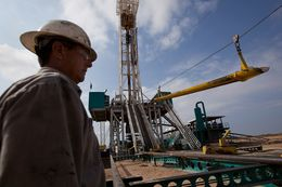 A worker waits to load a piece of pipe, or casing, that will be lowered into the well at a Chesapeake Energy drill site in Dimmit County, Texas in the Eagle Ford Shale.