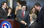 State Representative J.M. Lozano (center) shakes hands with Attorney General Greg Abbott as he announces that he's switching to the Republican Party during a press conference Thursday, March 18, 2012.