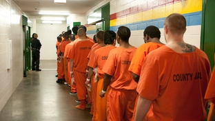 Inmates walk by in the Harris County Jail in 2011.