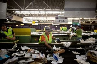 A Greenstar Recycling Center  employee removes plastic bags from a sort line in Garland, Texas, September 13, 2012.