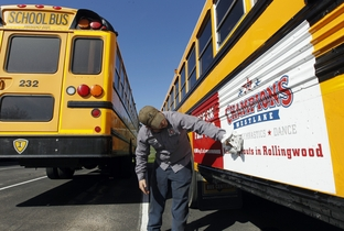 Eanes ISD school bus mechanic Chase Roberts washes the dirt off the advertising on Eanes ISD school buses in Westlake, Texas Tuesday February 14, 2012.