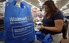 A cashier places groceries in a reusable bag for a customer at a Walmart in Brownsville.