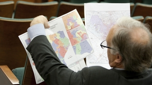 State Sen. Kirk Watson, D-Austin, looks at redistricting maps at a Senate hearing on May 13, 2011.