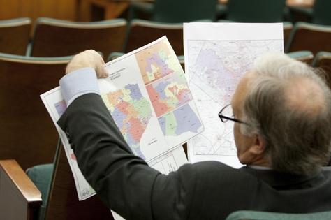 State Sen. Kirk Watson, D-Austin, looks at redistricting maps at a Senate hearing on May 13, 2011.
