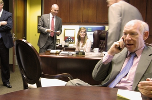 Bill White, on the phone in Grand Prairie Mayor Charles England's office. Behind him, from left to right, are Rep. Kirk England, son of the mayor, Theresa Woodward, his chief of staff, and the mayor himself.