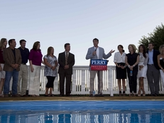 Gov. Rick Perry campaigns at a private reception in Cedar Rapids, Iowa, with family members standing by.