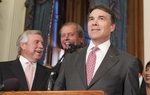 Gov. Rick Perry (r) looks at the crowd of reporters in the Governor's Reception Room as State Sen. Troy Fraser (l), R-Marble Falls, and Lt. Gov. David Dewhurst react at the Voter ID bill signing on May 27, 2011.