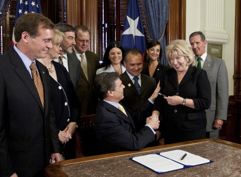 Gov. Rick Perry shakes hands with Sen. Jane Nelson R-Flower Mound after ceremonially signing Senate Bill 7