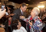 Governor Rick Perry greets Republican Linda Love at the Electric Park Ballroom on August 14th on his arrival in Iowa for three days of campaigning.