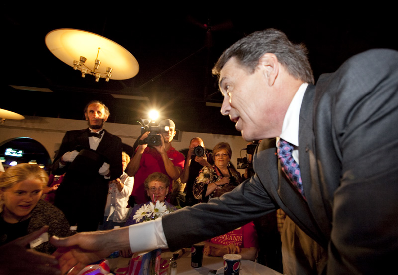 Governor Rick Perry shakes hands with patrons at the Electric Park Ballroom in Waterloo upon his arrival in Iowa on August 14, 2011