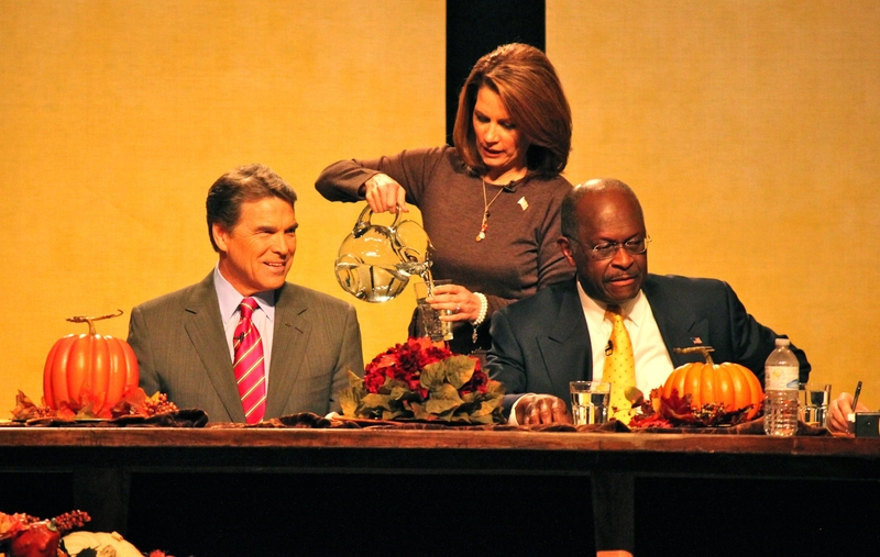 Rick Perry being served water by Michele Backmann at the Family Leader forum in Des Moines Iowa.