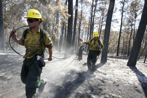 Firemen look for hot spots along Texas Highway 21 on September 13, 2011 after last week's devastating wildfires.