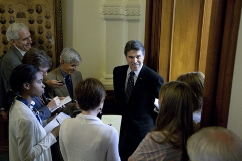Gov. Rick Perry (c) speaks with reporters outside the Senate Chamber on May 5, 2011.
