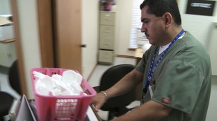 Clinic worker carries out box of birth control containers at Mission, TX clinic.