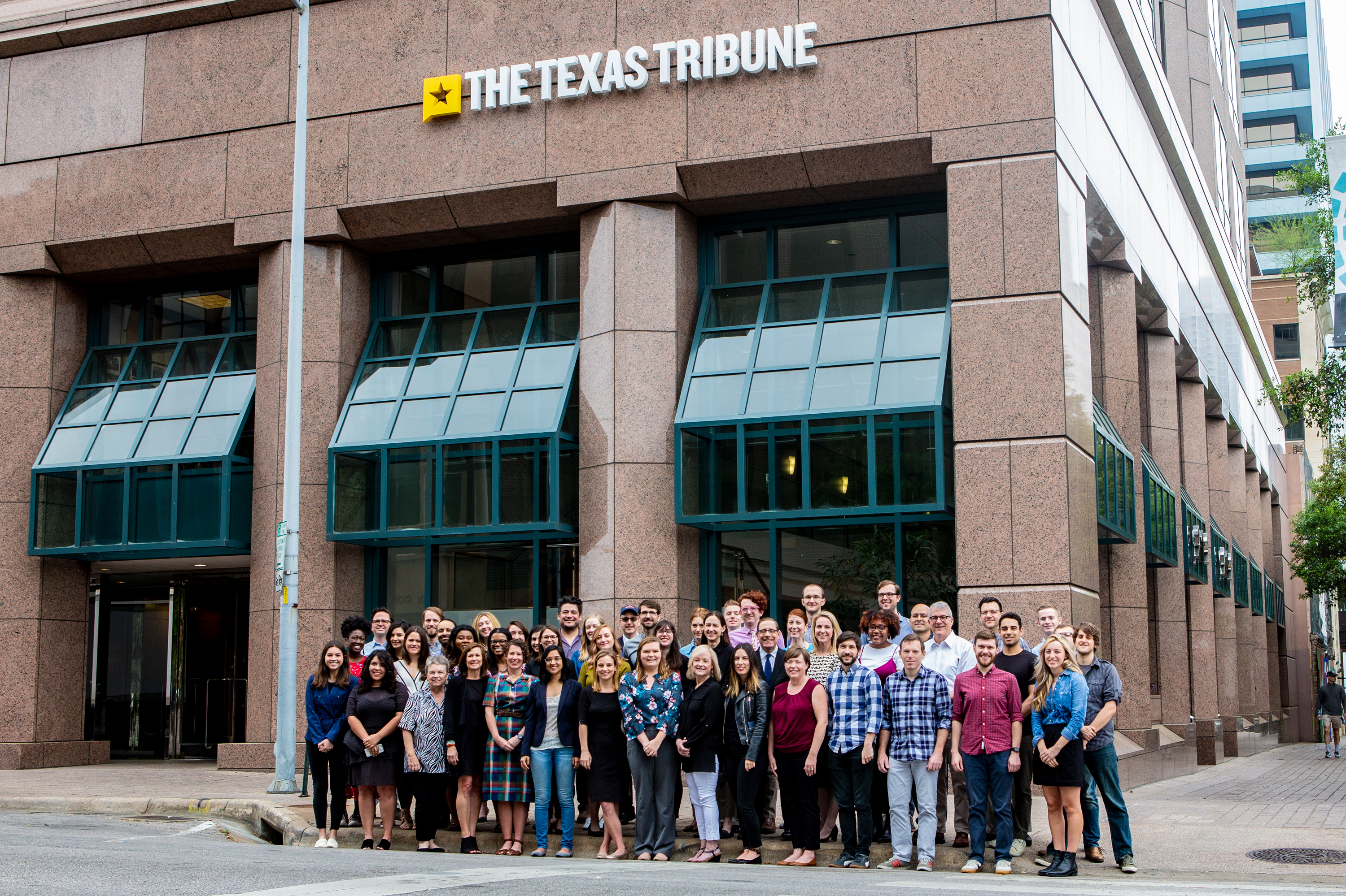 Members of the Texas Tribune staff stand together in front their headquarters.